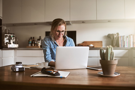 Smiling young female entrepreneur sitting at her kitchen table at home working on her small business with a laptop