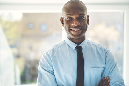 Smiling African businessman wearing a shirt and tie standing with his arms crossed in his home office Standard-Bild