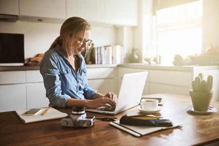 ノートパソコンで彼女の小さなビジネスで働いて自宅で彼女の台所のテーブルに座って焦点を当てた若い女性