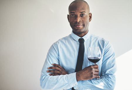 Smiling man in a shirt and tie standing with his arms crossed drinking a glass of red wine