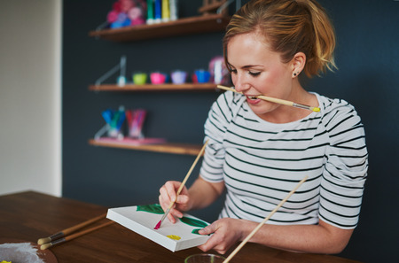 Creative woman painting different colours in her home