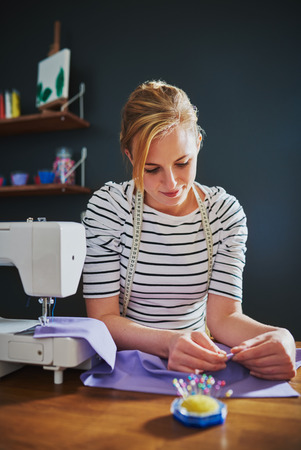 Female designer creating clothes on a sewing machine