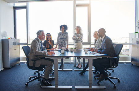 Diverse group of focused corporate executives talking together around a table during a meeting in a bright modern office