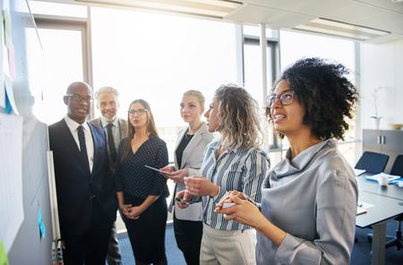 밝은 현대적인 사무실에서 화이트 보드에 함께 계획 및 전략 회의를 갖는 집중된 직장 동료들의 다양한 그룹