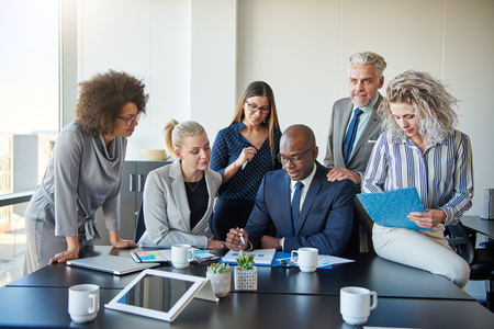 Group of focused businesspeople standing around their manager sitting at an office boardroom table reviewing charts and paperwork