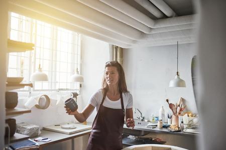 Sorrindo, femininas, artesão, ficar, sozinha, em, dela, criativo, oficina, segurando, um, recentemente, feito, pedaço, de, vitrificado, cerã ¢ icas