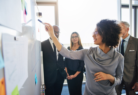 Diverse group of focused businesspeople brainstorming together on a whiteboard during a strategy meeting in a bright modern office