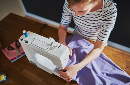 Overhead view of creative woman with sewing machine