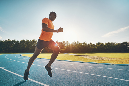 Focused young African male runner in sportswear sprinting alone along a running track on a sunny day Stock Photo