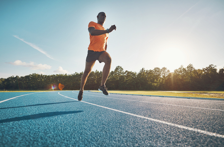 Fit young African male athlete in sportswear racing alone down a running track on a sunny day Stock Photo