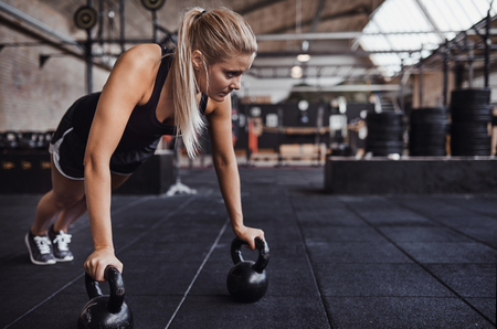 Fit young blonde woman in exercise clothing working out alone with weights in a gym
