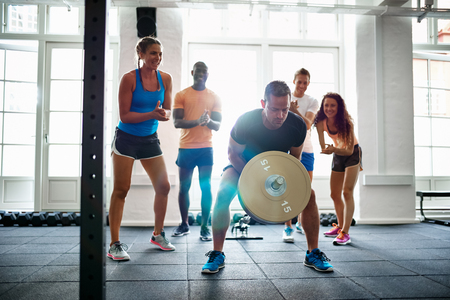 Fit young man straining to lift weights in a gym with a diverse group of friends cheering him on in the background