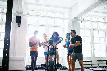 Diverse group of people cheering on their friend riding a stationary bike while working out together in a gym Stock Photo