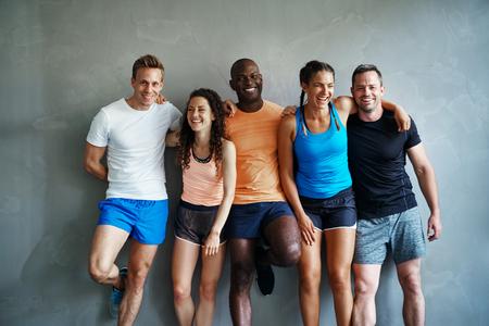 Grupo sonriente de amigos deportivos en ropa deportiva riendo mientras está de pie del brazo juntos contra la pared de un gimnasio después de un entrenamiento Foto de archivo