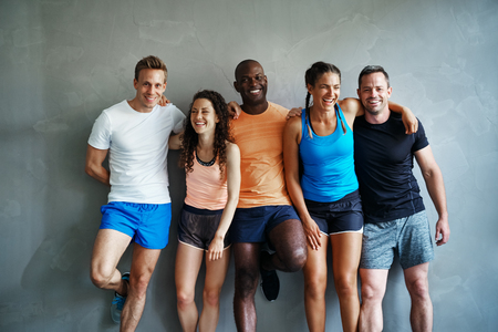 Smiling group of sporty friends in sportswear laughing while standing arm in arm together against the wall of a gym after a workout