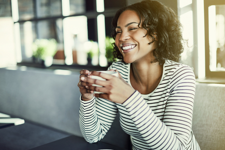 Laughing young African woman sitting alone at a table in a cafe enjoying a fresh cup of coffee Stok Fotoğraf - 95919720
