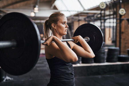 Fit young blonde woman in exercise clothing focused on lifting a barbell while weightlifting alone in a gym