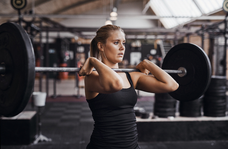 Fit and focused young blonde woman in workout clothing weightlifting with a barbell alone in a gym Фото со стока