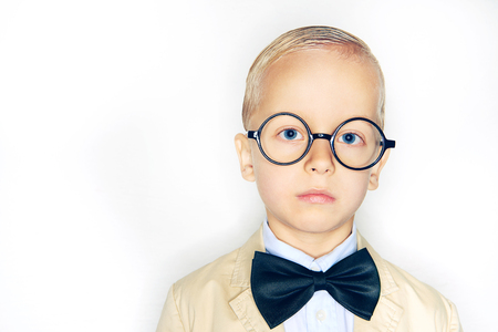 Little boy in formal suit and glasses looking at camera on studio background.