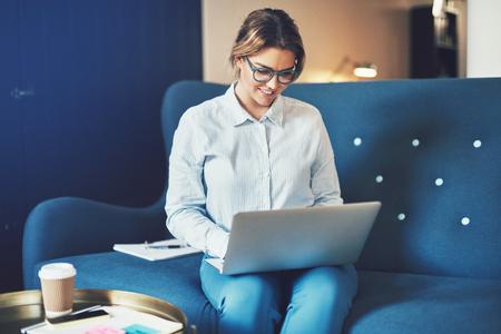 自宅のソファに座りながら、ラップトップでオンラインで作業する若いビジネスウーマンを笑顔 写真素材