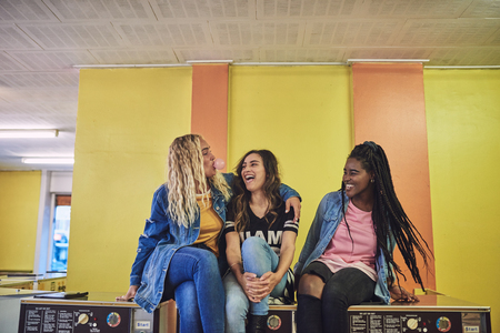 Three young girlfriends sitting together on washing machines in a laundromat laughing and blowing bubbles with chewing gum