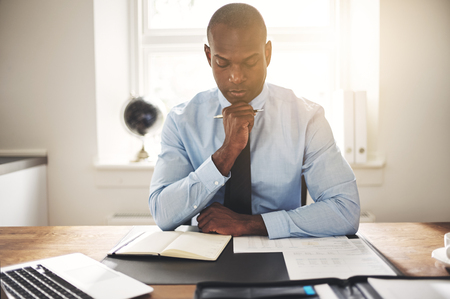 Focused young African businessman wearing a shirt and tie sitting at his desk in an office reading through paperwork
