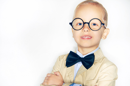 Studio shot of little confident boy posing with hands crossed and looking at camera confidently.  Stock Photo