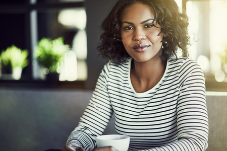 Young African woman smiling confidently while sitting alone at a table in a cafe enjoying a fresh cup of coffee