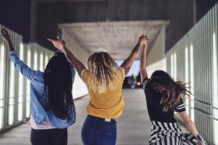 Retrovisor de um grupo de diversas jovens amigas se divertindo enquanto andam de mãos dadas juntos por uma passarela na cidade à noite Foto de archivo