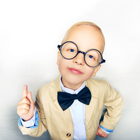Little boy in suit and glasses posing with finger up and looking confidently at camera in studio.