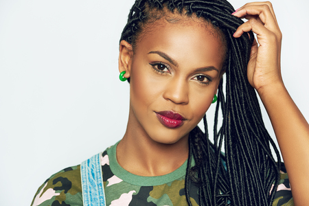 Front portrait of beautiful African-American woman model with accurate black dreadlocks and make-up, with her hand to her hair, wearing green camouflage shirt Banque d'images
