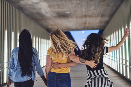 Rearview of a group of young friends having fun while walking arm in arm together down a walkway in the city at night Banco de Imagens