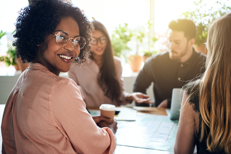 Smiling African businesswoman sitting at an office table looking over her shoulder with colleagues working in the background 스톡 콘텐츠