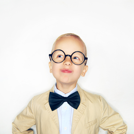 Studio shot of little boy in glasses and formal suit making faces and looking away.  Banco de Imagens