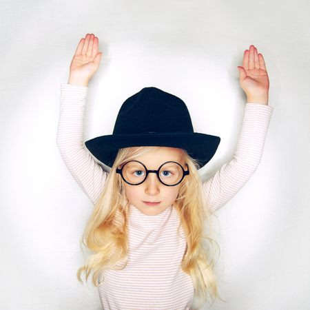 Little adorable girl in hat and glasses holding hands up and looking seriously at camera in studio.