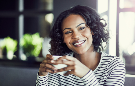 Young African woman smiling while sitting alone at a table in a cafe enjoying a fresh cup of coffee