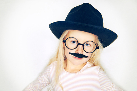 Studio shot of girl in black hat and glasses with fake moustache on face looking at camera.