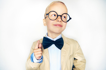 Studio shot of little satisfied boy holding finger up looking away on studio background.  Imagens