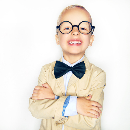 Little cheerful boy in glasses and suit posing with hands crossed on studio background.