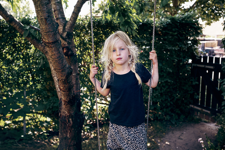 Cute little blonde girl playing alone on a tree swing in her backyard on a sunny day Stockfoto