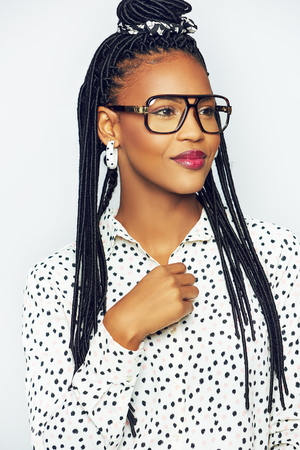 Head and shoulders portrait of ashionable young black woman in glasses looking to side, white background