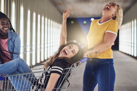 Laughing young woman being pushed in a shopping cart at night down a walkway in the city by girlfriends