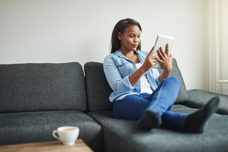 Young African woman browsing online with a digital tablet while relaxing on the sofa in her living room at home