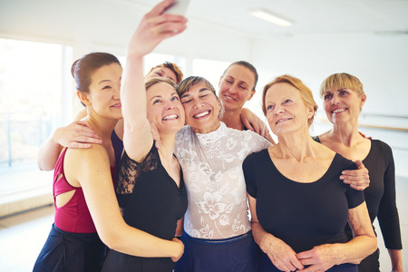 Mixed age group of smiling women standing arm in arm together in a dance studio taking a selfie