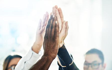 明るいモダンなオフィスで一緒にハドルに立ちながら、ビジネス仲間の多様なグループが互いに高いフィビング
