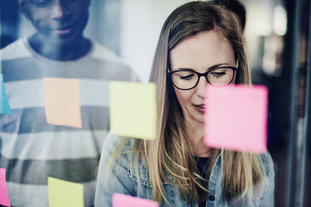 Young businesswoman brainstorming with sticky notes on a glass wall while standing in an office with colleagues in the background Stok Fotoğraf