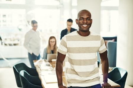 Young African designer smiling confidently while leaning on a table in an office with colleagues working in the background