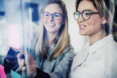 Two young businesswomen standing in a modern office brainstorming together with sticky notes on a glass wall
