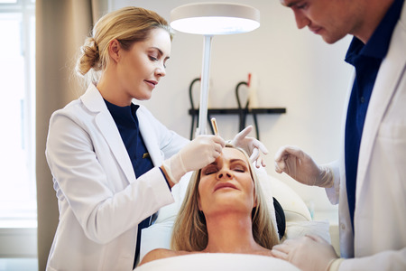 Two young doctors discussing a cosmetic surgery procedure on the face of a mature woman lying on a table in a clinic