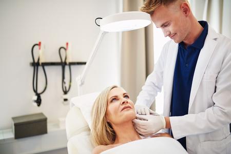 Jeune homme médecin effectuant une injection au menton d'une femme mature allongée sur une table dans une clinique de beauté